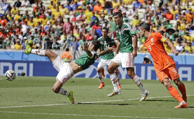 Mexico's Rafael Marquez (4) attempts to kick the ball ahead of defender Mexico's Raul Jimenez during the World Cup round of 16 soccer match between the Netherlands and Mexico at the Arena Castelao in Fortaleza, Brazil, Sunday, June 29, 2014. (AP Photo/Felipe Dana)