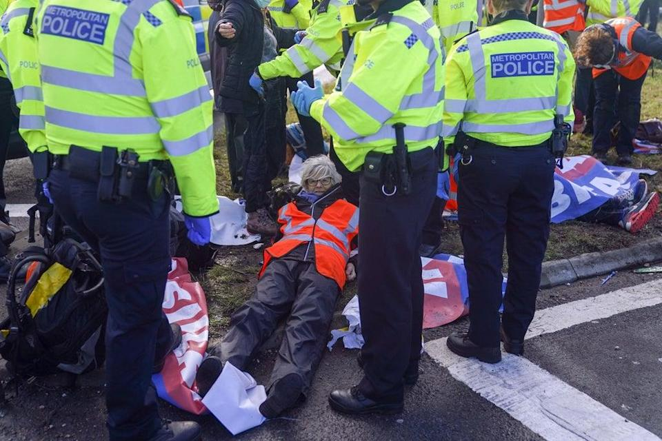 Police officers detain a protester from Insulate Britain occupying a roundabout leading from the M25 motorway to Heathrow Airport in London (Steve Parsons/PA) (PA Wire)