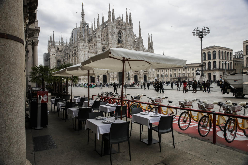 FILE - In this Wednesday, Oct. 21, 2020 file photo, empty tables of a restaurant in the Duomo Square in Milan, Italy. The coronavirus pandemic is gathering strength again in Europe and, with winter coming, its restaurant industry is struggling. The spring lockdowns were already devastating for many, and now a new set restrictions is dealing a second blow. Some governments have ordered restaurants closed; others have imposed restrictions curtailing how they operate. (AP Photo/Luca Bruno, File)