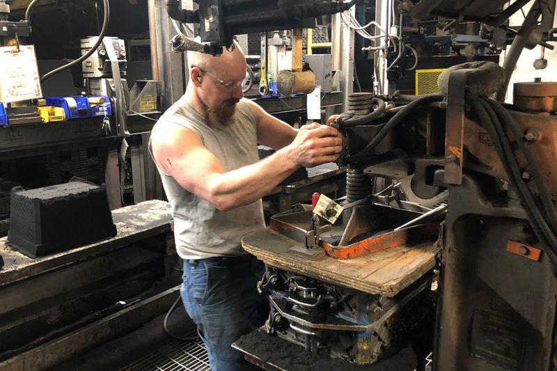 A worker uses a hydraulic press to squeeze sand into a mold that will be used to make parts at Kirsh Foundry Inc. in Beaver Dam Wisconsin