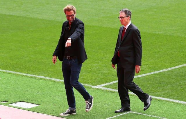 Liverpool manager Jurgen Klopp and principal owner John W Henry walk on the pitch at Anfield