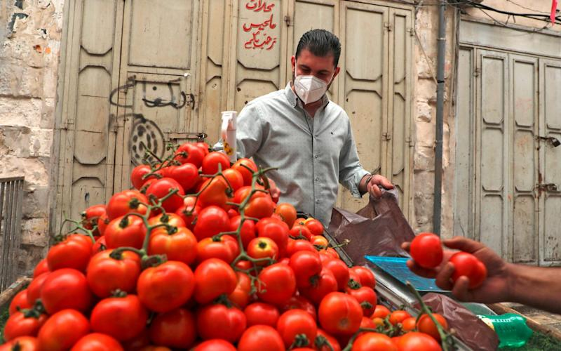 A Palestinian man buys from a street vendor in the city of Nablus - JAAFAR ASHTIYEH/AFP