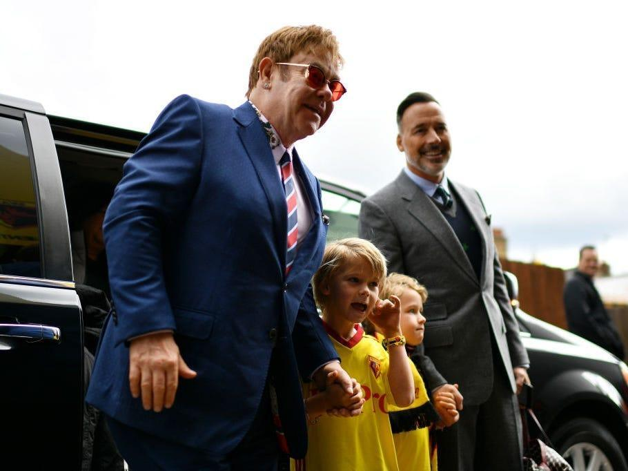 Elton John exits a car with his husband and sons.