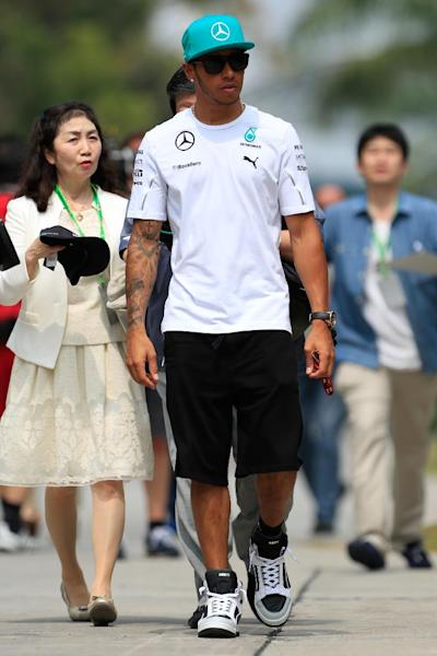 Mercedes driver Lewis Hamilton of Britain walks at the paddock as he arrives for the third practice session and qualifying session for Sunday's Malaysian Formula One Grand Prix at Sepang International Circuit in Sepang, Malaysia, Saturday, March 29, 2014. (AP Photo/Peter Lim)