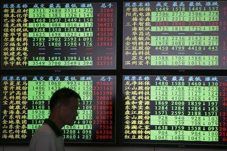 An investor walks past as information displayed on an electronic screen at a brokerage house in Shanghai, China, July 3, 2015. REUTERS/Aly Song