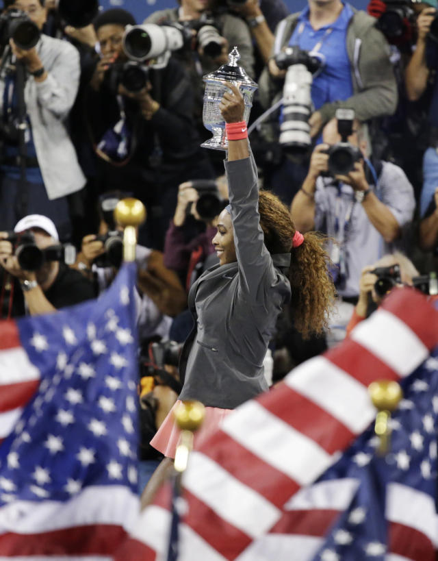 Serena Williams holds up the championship trophy after beating Victoria Azarenka, of Belarus, during the women's singles final of the 2013 U.S. Open tennis tournament, Sunday, Sept. 8, 2013, in New York. (AP Photo/Kathy Willens)