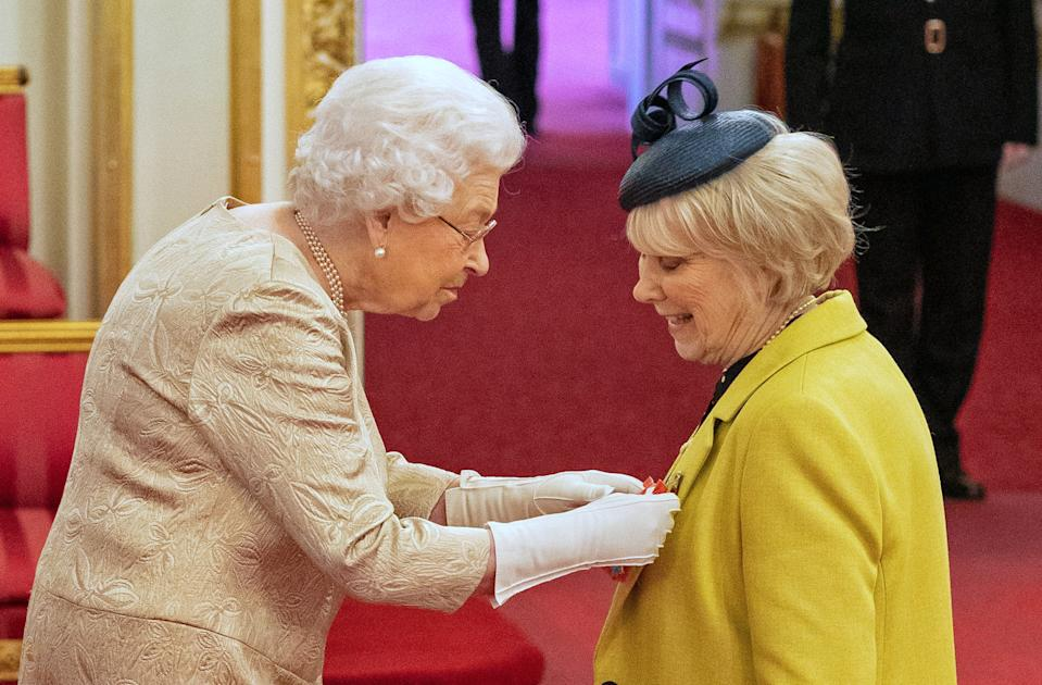 Queen Elizabeth II wears gloves as she awards the CBE (Commander of the Order of the British Empire) to Miss Anne Craig, known professionally as actress Wendy Craig, during an investiture ceremony at Buckingham Palace in London.