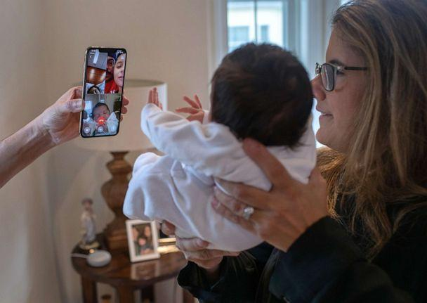PHOTO: Stamford Elementary school teacher Luciana Lira holds Neysel while showing the newborn for the first time to his mother Zully, a Guatemalan asylum seeker, and her son Junior, 7, via Zoom on April 20, 2020, in Stamford, Conn. (John Moore/Getty Images)