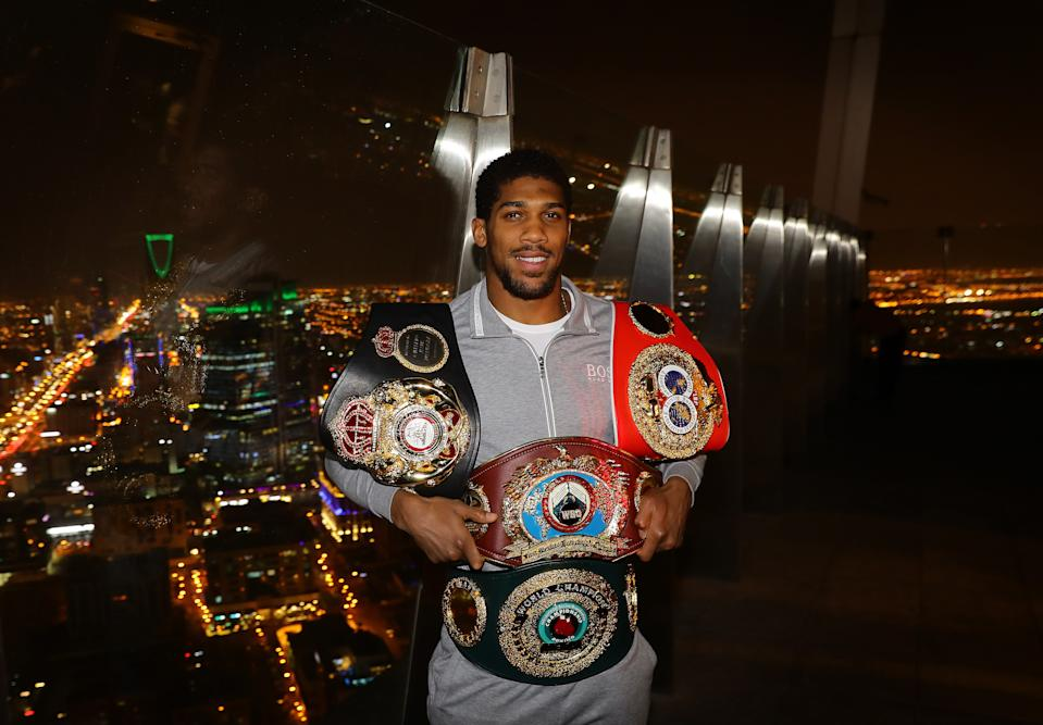 Anthony Joshua with his four title belts in front of a dark city skyline.