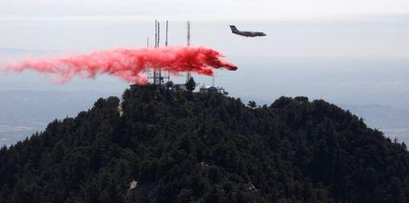 An airplane drops fire retardant while battling the Wilson Fire near Mount Wilson in the Angeles National Forest in Los Angeles, California, U.S. October 17, 2017. REUTERS/Mario Anzuoni