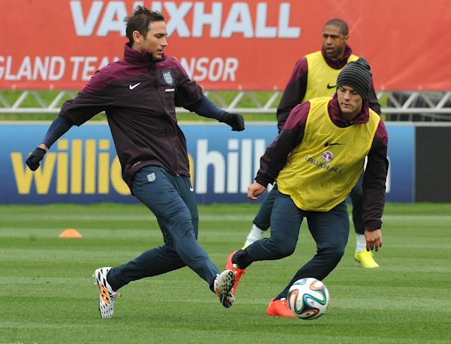 England national soccer team players Frank Lampard, left, and Jack Wilshere kick a ball during a training session at George's Park in Burton on Trent, England, Tuesday, May 27, 2014. England play an international friendly soccer match against Peru at Wembley on Friday. (AP Photo/Rui Vieira)
