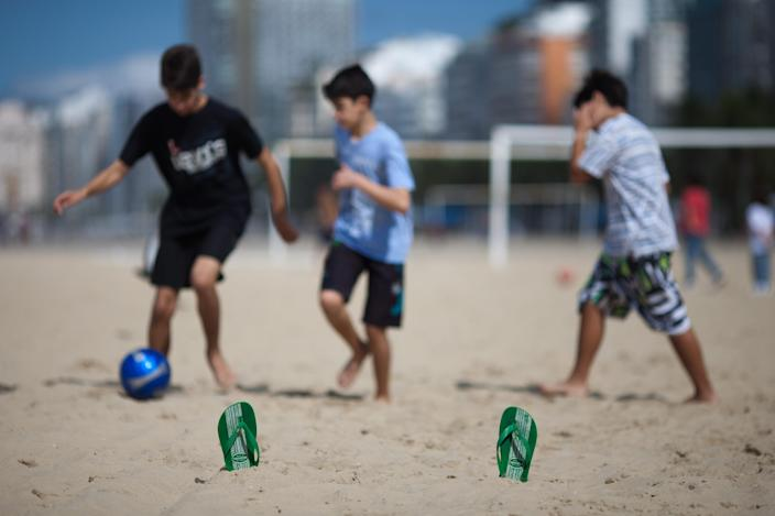 In this July 17, 2012 photo, youths play soccer using Havaianas sandals to mark the goal area on Copacabana beach in Rio de Janeiro, Brazil. In Brazil, literally everyone wears Havaianas, the now world-famous brand of rubber and plastic flip-flops that's celebrating its 50th birthday this year. (AP Photo/Felipe Dana)