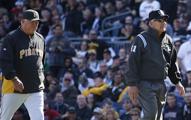 Pittsburgh Pirates manager Clint Hurdle, left, follows first base umpire Bob Davidson, from the field after he requested a review on a safe call at first on a pickoff attempt in the tenth inning of the opening day baseball game against the Chicago Cubs on Monday, March 31, 2014, in Pittsburgh. Cubs' Emilio Bonifacio was called safe but the call was overturned on the review requested by Hurdle and Bonifacio was ruled out. The Pirates won 1-0 in ten innings.(AP Photo/Keith Srakocic)