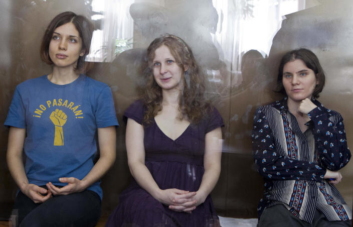 In this Wednesday, Aug. 8, 2012 file photo feminist punk group Pussy Riot members, from left, Nadezhda Tolokonnikova, Maria Alekhina and Yekaterina Samutsevich sit in a glass cage at a court room in Moscow, Russia. Three members of Pussy Riot were jailed in March and charged with hooliganism motivated by religious hatred after their punk performance against President Putin in Moscow's main cathedral. Theyare awaiting the verdict on Friday, Aug. 17, 2012. (AP Photo/Misha Japaridze, file)