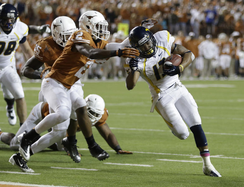 West Virginia's Andrew Buie, right, runs through Texas defender Mykkele Thompson (2) to score during the fourth quarter of an NCAA college football game on Saturday, Oct. 6, 2012, in Austin, Texas. West Virginia won 48-45. (AP Photo/Eric Gay)