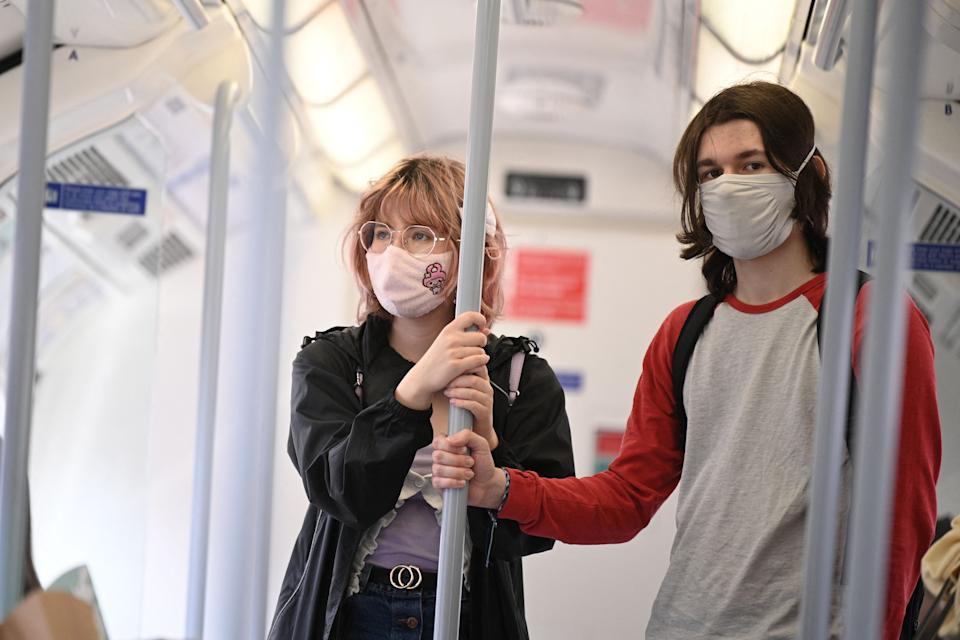 Commuters wearing protective face coverings to combat the spread of the coronavirus, travel on a Transport for London (TFL) Underground train in central London on July 5, 2021. - British Prime Minister Boris Johnson on Monday unveils plans to lift most of the latest health restrictions from 19 July, including the mandatory wearing of face coverings on some forms of public transport. (Photo by DANIEL LEAL-OLIVAS / AFP) (Photo by DANIEL LEAL-OLIVAS/AFP via Getty Images)