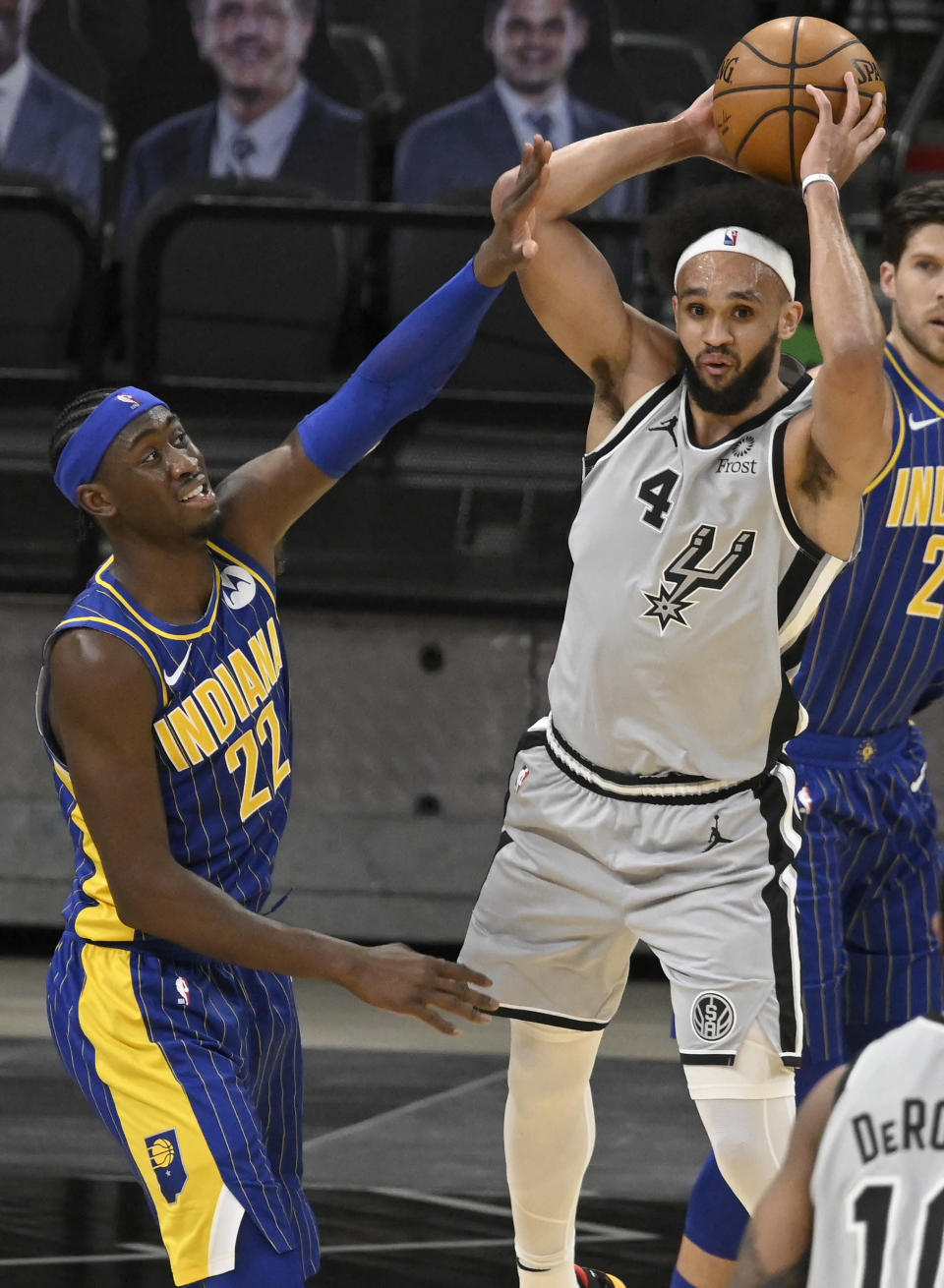 San Antonio Spurs' Derrick White (4) looks to pass as he is defended by Indiana Pacers' Caris LeVert during the second half of an NBA basketball game on Saturday, April 3, 2021, in San Antonio. (AP Photo/Darren Abate)