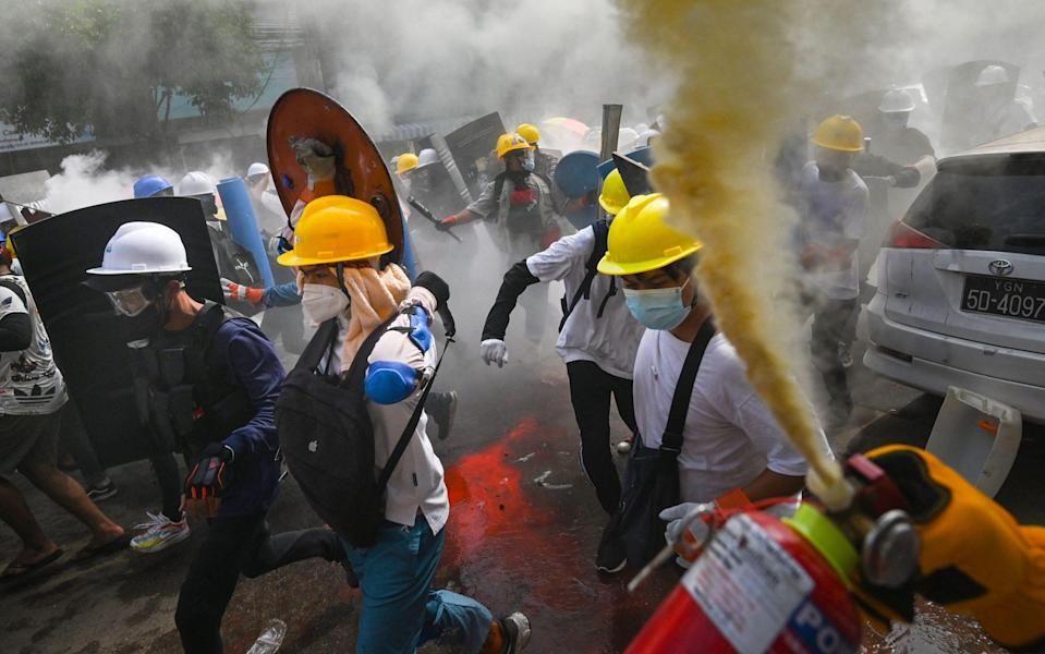 A protester uses a fire extinguisher as others holding homemade shields run during a demonstration - AFP