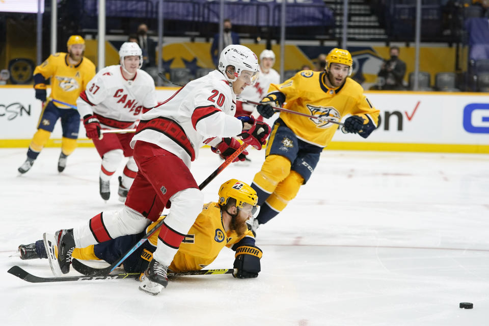 Nashville Predators defenseman Ryan Ellis (4) falls under Carolina Hurricanes center Sebastian Aho (20) as they battle for the puck during the first period in Game 3 of an NHL hockey Stanley Cup first-round playoff series Friday, May 21, 2021, in Nashville, Tenn. (AP Photo/Mark Humphrey)