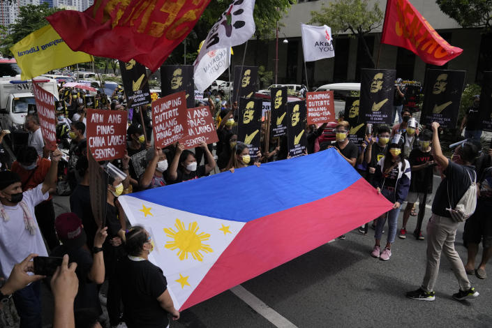 Protesters shout slogans as they hold a Philippine flag during a rally in front of the Chinese Consulate in Makati city, Philippines on Monday, July 12, 2021. The demonstration was held to commemorate the 5th anniversary of the Arbitral Ruling in The Hague by the UNCLOS (United Nations Convention on the Law of the Sea) granting the Philippines the exclusive right to fish within its Exclusive Economic Zone or EEZ. (AP Photo/Aaron Favila)