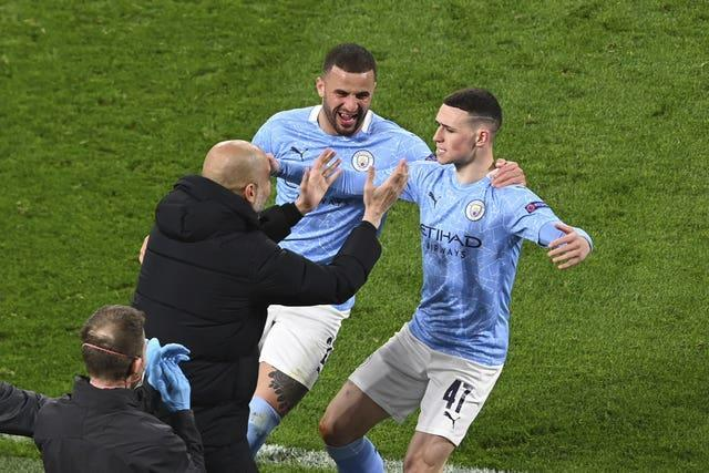 Phil Foden celebrates (right) his crucial goal with manager Pep Guardiola (left)