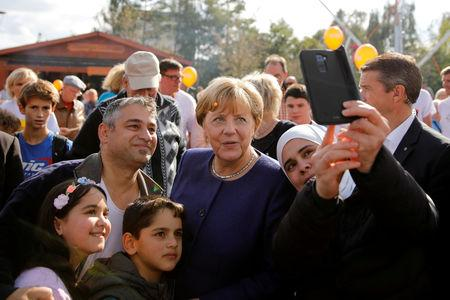 FILE PHOTO: German Chancellor Angela Merkel, a top candidate of the Christian Democratic Union Party (CDU) for the upcoming general elections poses for a selfie during an election rally in Stralsund, Germany September 16, 2017. REUTERS/Axel Schmidt/File Photo