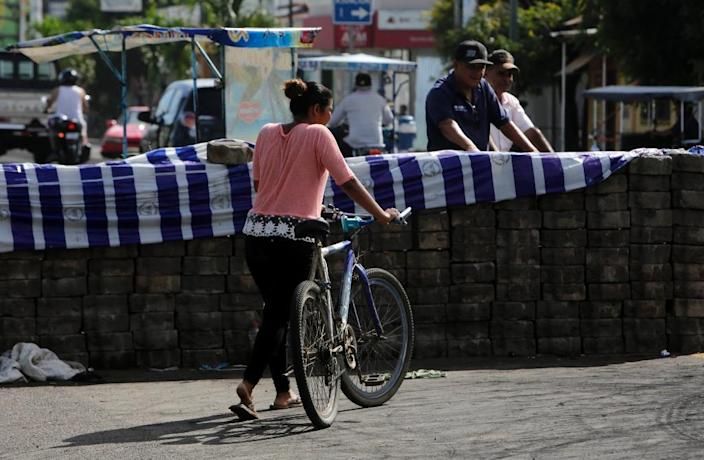 A woman passes next to a barricade in the city of Sebaco (AFP Photo/Inti Ocon)