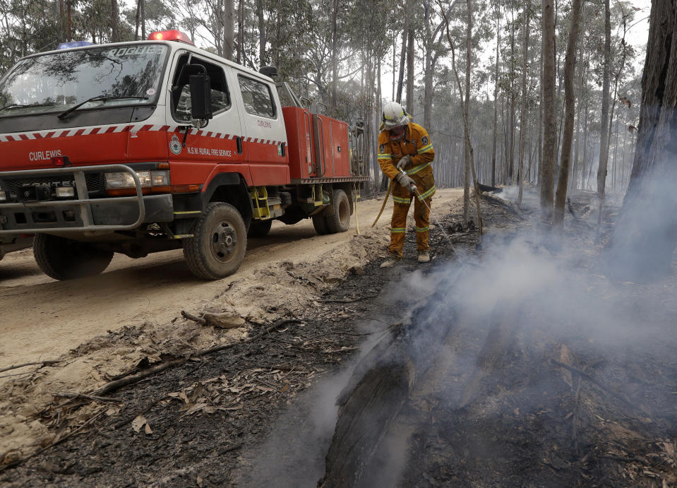 A firefighter patrols a controlled fire as they work at building a containment line at a wildfire near Bodalla, Australia, Sunday, Jan. 12, 2020. Authorities are using relatively benign conditions forecast in southeast Australia for a week or more to consolidate containment lines around scores of fires that are likely to burn for weeks without heavy rainfall. (AP Photo/Rick Rycroft)