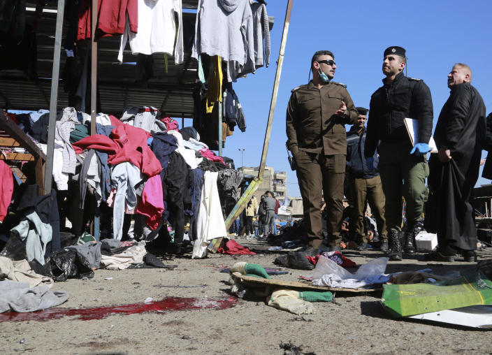 Security forces work at the site of a deadly bomb attack in a market selling used clothes, Iraq, Thursday, Jan. 21, 2021. Iraq's military said twin suicide bombings have ripped through a busy market in Iraq's capital, killing over 2 dozen and wounding over 70 with some in serious condition. (AP Photo/Hadi Mizban)