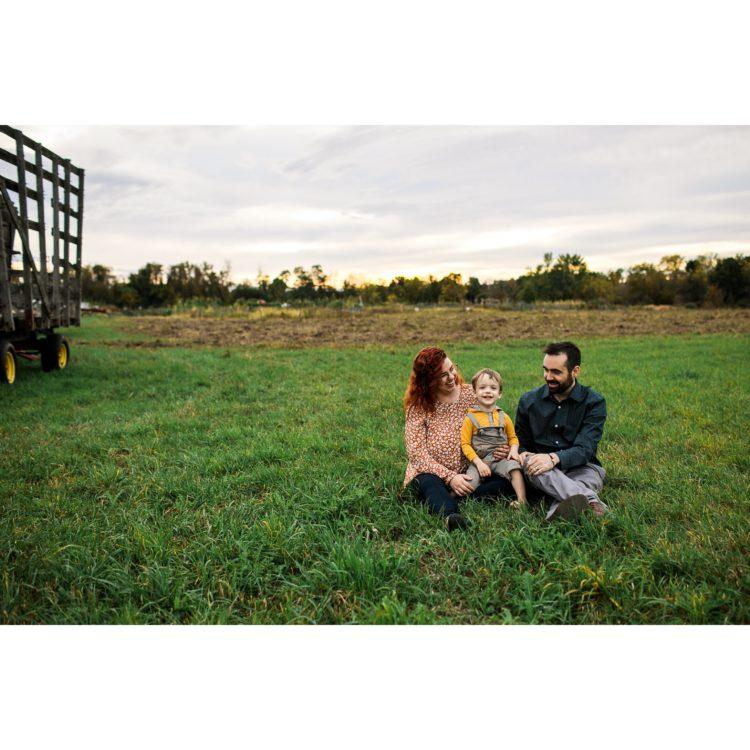 parents sitting with their son in a green field of grass