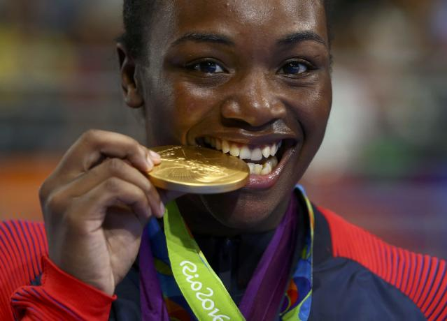 2016 Rio Olympics - Boxing - Victory Ceremony - Women's Middle (75kg) Victory Ceremony - Riocentro - Pavilion 6 - Rio de Janeiro, Brazil - 21/08/2016. Gold medallist Claressa Shields (USA) of USA bites her medal from Rio 2016. REUTERS/Peter Cziborra FOR EDITORIAL USE ONLY. NOT FOR SALE FOR MARKETING OR ADVERTISING CAMPAIGNS.