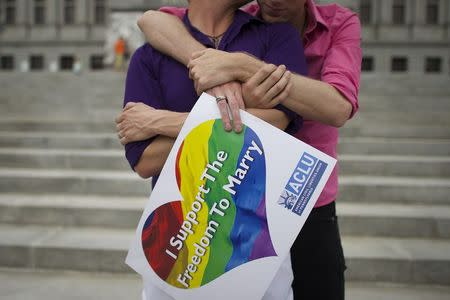 Mike Woods, 28, and Brandon Parsons, 30, embrace on the Pennsylvania State Capital steps following a rally with gay rights supporters after a ruling struck down a ban on same sex marriage in Harrisburg, Pennsylvania, May 20, 2014. REUTERS/Mark Makela