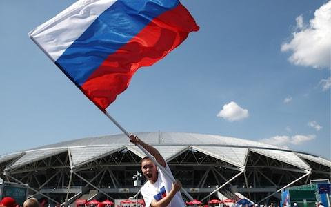 A fan of Team Russia waves the Russian flag ahead of a 2018 FIFA World Cup Group A football match between Russia and Uruguay at Samara Arena - Credit: Getty Images