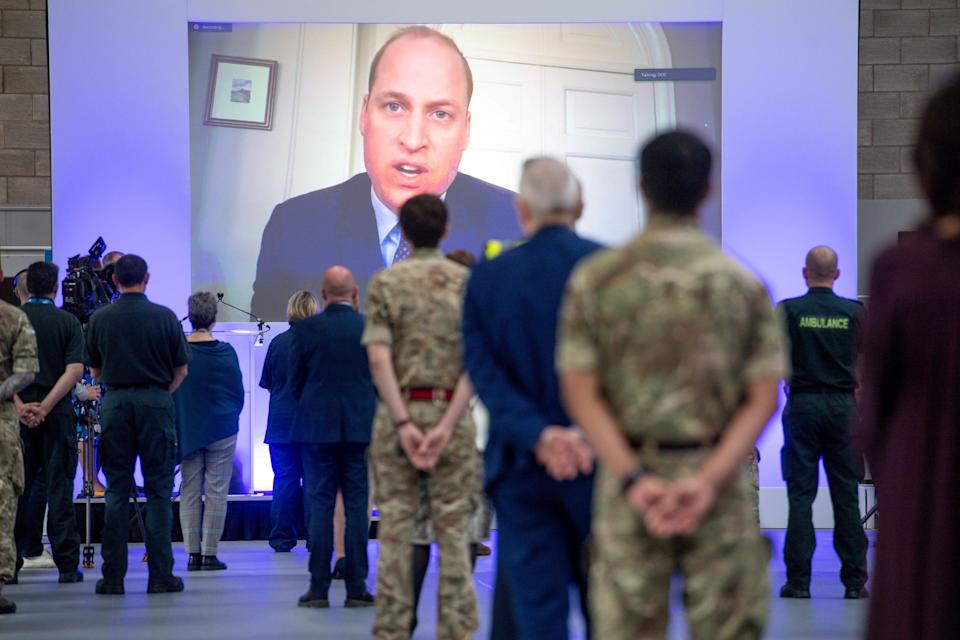 People observe social distancing measures as they stand amongst Hospital cubicles, as a giant screen displays an image of Britain's Prince William, Duke of Cambridge, as he speaks via video-link during the official opening of the NHS Nightingale Hospital Birmingham, setup inside the National Exhibition Centre (NEC) in Birmingham, central England on April 16, 2020, to help Britain's National Health Service cope with an expected influx of patients during the novel coronavrius pandemic. - The British government was on Thursday expected to extend a nationwide lockdown for another three weeks, amid signs the coronavirus outbreak is peaking, but warnings of more deaths to come. (Photo by Jacob King / POOL / AFP) (Photo by JACOB KING/POOL/AFP via Getty Images)