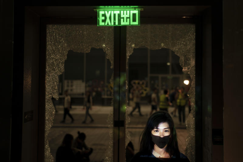 In this Oct. 16, 2019, photo, a protester who identified herself as Sonia, poses for a portrait next to a broken glass door as a projector displays a photograph, previously taken during the unrest, over her at a protest in Hong Kong. For many protesters, identity is entwined with surveillance. Their signature masks, umbrellas and top-to-bottom black outfits shield them not only from physical threats like the riot police's tear gas and rubber bullets, but also from the invisible dangers of government identification and tracking. (AP Photo/Felipe Dana)