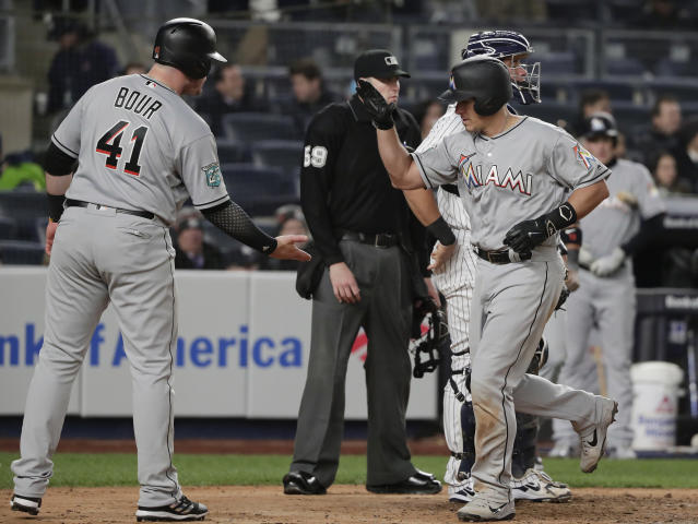 Miami Marlins' J.T. Realmuto, right, is congratulated at home plate by Justin Bour (41) after hitting a three-run home run against the New York Yankees during the fifth inning of a baseball game Tuesday, April 17, 2018, in New York. (AP Photo/Julie Jacobson)