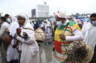 Women bring items to give to the youth joining the Defense Forces, at Meskel Square, in Addis Ababa, Ethiopia, Tuesday, July 27 2021. A repatriation program is underway for young people from Ethiopia who have decided to join the Defense Forces. (AP Photo)