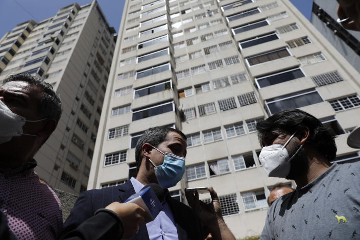 Opposition leader Juan Guaido speaks to the press at his residential building in Caracas, Venezuela, Monday, July 12, 2021. Guaido said security forces threatened his driver when he and his driver arrived home Monday. (AP Photo/Ariana Cubillos)