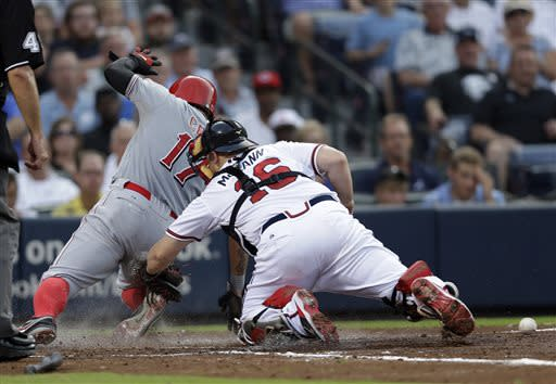 iCincinnati Reds' Shin-Soo Choo (17) scores on a Joey Votto fly ball as the ball gets away from Atlanta Braves catcher Brian McCann (16) in the third inning of a baseball game on Thursday, July 11, 2013, in Atlanta. (AP Photo/John Bazemore)