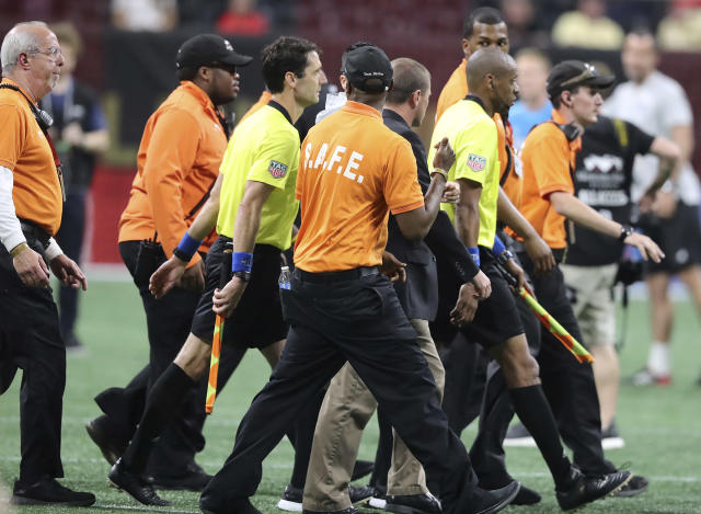 Security guards escort the game officials off the pitch after a heated MLS soccer match between Atlanta United and Sporting Kansas City on Wednesday, May 9, 2018, in Atlanta. (Curtis Compton/Atlanta Journal-Constitution via AP)