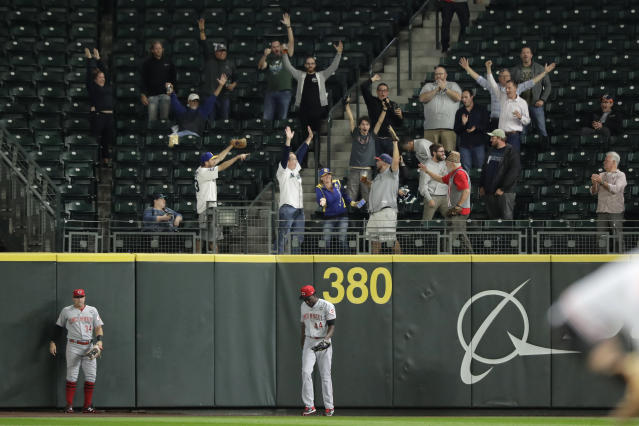Cincinnati Reds right fielder Aristides Aquino (44) stands at the wall as fans celebrate after Seattle Mariners' Kyle Lewis hit a three-run home run during the seventh inning of a baseball game, Wednesday, Sept. 11, 2019, in Seattle. Lewis ended a no-hitter by Reds pitcher Sonny Gray. (AP Photo/Ted S. Warren)