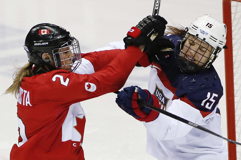 Meghan Agosta-Marciano of Canada (2) and Anne Schleper of the United States (15) mix it up during the second period of the women's gold medal ice hockey game at the 2014 Winter Olympics, Thursday, Feb. 20, 2014, in Sochi, Russia. (AP Photo/Petr David Josek)