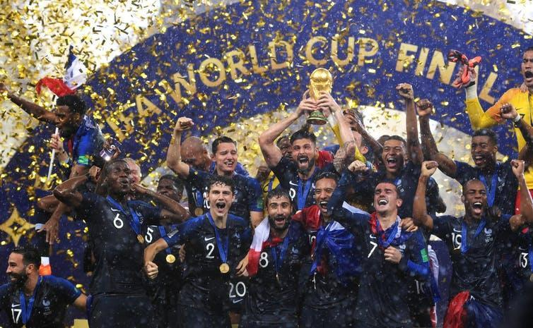The French football team celebrating in a cloud of confetti.
