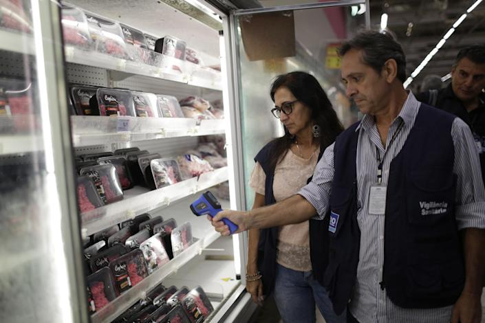 Municipal Sanitary Surveillance wrokers inspect meat at a supermarket in Rio de Janeiro, Brazil, Monday, March 20, 2017. The European Union's spokesman in Brazil says the union is temporarily halting some imports of Brazilian meat amid an investigation into a massive scheme of meat adulteration, which involved some of the country's largest producers. (AP Photo/Silvia Izquierdo)