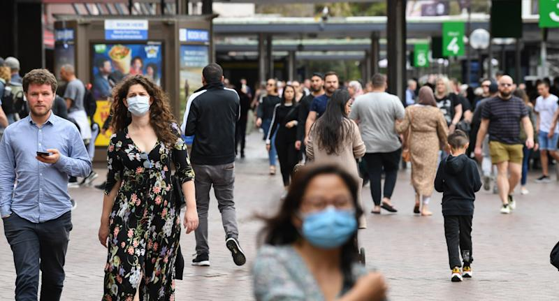 A photo shows a crowd of people, some wearing face masks, walking in Sydney, Australia.