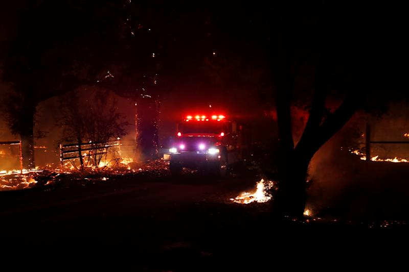 A fire engine drives on a road with active fire on both sides during the wind-driven Kincade Fire in Santa Rosa, California, Oct. 27, 2019. (Photo: Stephen Lam/Reuters)