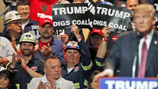 In this May 5, 2016 photo, coal miners wave signs as Republican presidential candidate Donald Trump speaks during a rally in Charleston, W.Va.(AP Photo/Steve Helber)