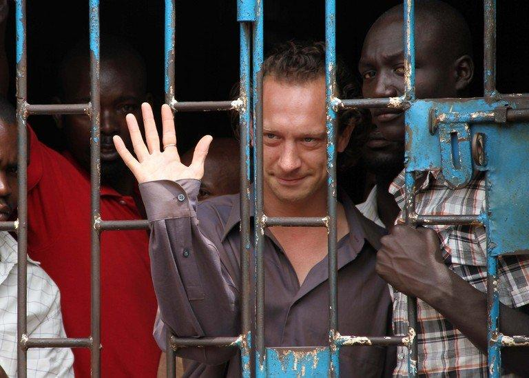British theatre producer David Cecil waves from a cell at the Makindye Court on September 13, 2012 in Kampala