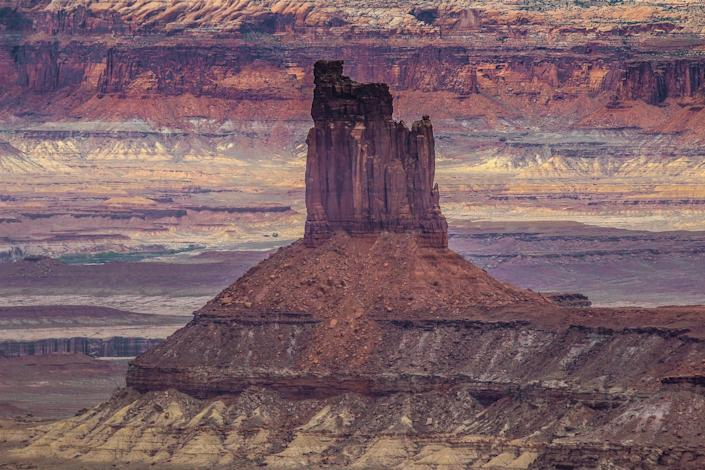 The impressive reddish-brown tones of rugged Candlestick Tower pop during the early hours of the day from the Island of the Sky district panoramic overlook in Canyonlands. The Wingate Sandstone tower soars to a height of 450 feet. You'll notice that the top chimney shape is red, the middle section is shades of brown, while the bottom is white.