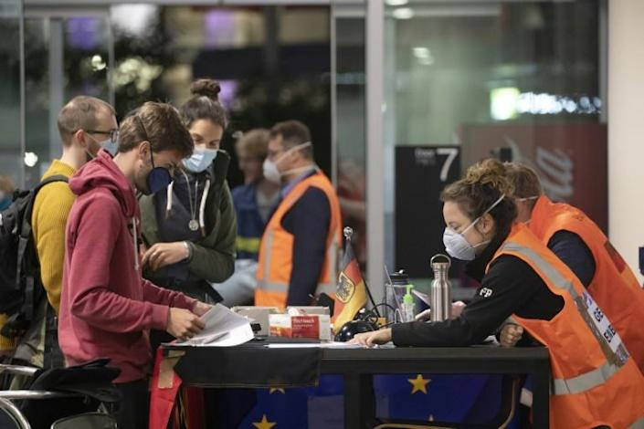 Embassy staff check documents of German tourists as they prepare to check in for a special flight to Frankfurt from Christchurch in New Zealand (AFP Photo/Sanka VIDANAGAMA)